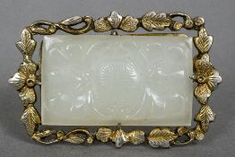 An unmarked gilt and white metal mounted carved white jade brooch Centrally set and carved with