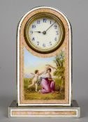 A pink enamel decorated desk clock The white circular dial with Arabic numerals above a figural
