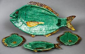 A French majolica dinner service The plates formed as various fish, the sauceboat as a dolphin.