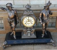 A bronzed mantel clock Surmounted with cavaliers.  52 cm high.