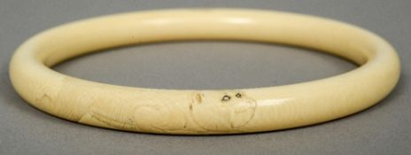A Japanese carved ivory bangle Decorated with twin monkeys.  10.5 cm diameter.