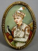 A 19th century Indian miniature portrait of a nobleman holding falcon Housed in a gilt brass frame.