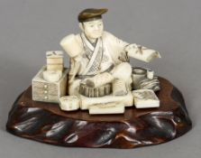 A 19th century carved ivory okimono Formed as a scholar at work,