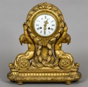 A late 19th/early 20th century carved giltwood mantel clock The white enamelled dial with Roman
