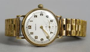 A 1940s 9 ct gold cased gentleman's wristwatch by Marvin The silvered dial with Arabic numerals and