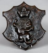 A carved wooden shield shaped panel Worked with a lion holding a sword surmounted with a crown,