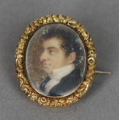 An early 19th century portrait miniature  of a gentleman Housed in a yellow metal necklace clasp