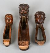 Three 19th century carved treen stocks One carved with a lion mask, one a female bust,