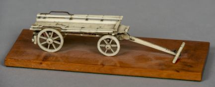 A 19th century Prisoner of War bone model of a cart Mounted on a later mahogany plinth base.  25.