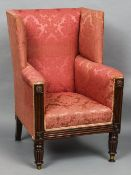 An early 19th century mahogany wing back armchair With faded red upholstery above the reeded arms,