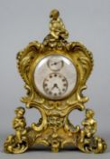 A small gilt bronze desk clock With scroll cast and putto decoration with a silvered regulator dial.