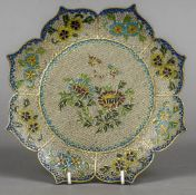 A plique-a-jour plate Of lobed form, decorated with flowers. 23 cm diameter.