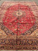 A Kashan wool carpet The wine red field enclosing a central medallion with pendant palmettes with