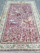 A Middle Eastern wool carpet The wine red field extensively filled with exotic birds amongst