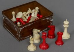 A late 19th/early 20th century carved and red stained Staunton pattern chess set In mahogany box.