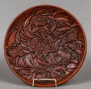 A Chinese cinnabar lacquer charger Extensively carved with lotus flowers and foliage opposing