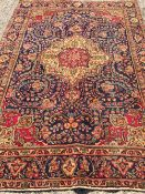 A Tabriz wool carpet The midnight blue field enclosing a central medallion with pendant palmettes