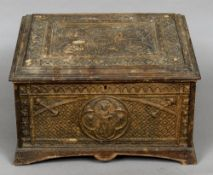 A 19th century carved box The hinged lid and sides with Gothic style panels with cherub masks.