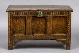 An 18th century three panelled oak coffer The moulded rectangular top above the panelled front with