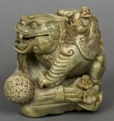 A Chinese carved soapstone group Worked as figures attending an oversized mythical beast.