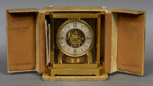 A boxed Atmos clock Of typical form, the silvered dial with Arabic numerals and batons. 23.