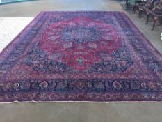 An Isfahan wool carpet The wine red field enclosing an arabesque medallion with pendant palmettes
