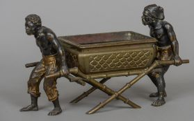 A patinated and cold painted bronze centrepiece Formed as two North African figures carrying a