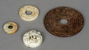 Four Chinese carved hardstone roundels The largest 10 cm diameter.