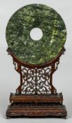 A Chinese carved green hardstone bi-disc Of typical form,