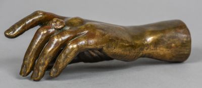 A patinated bronze model of a hand Naturalistically modelled wearing a ring. 22.5 cm long.