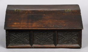 A 17th/18th century carved oak slope topped Bible box The hinged top with sloping front above three