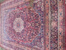 A Tabriz wool carpet The wine red field enclosing a central ivory medallion with pendant palmettes