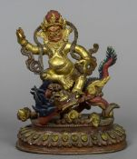 A Chinese painted bronze model of a deity Modelled seated astride a dragon. 18 cm high.