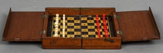 A 19th century mahogany travelling chess set The pieces carved bone and stained. 20.5 cm wide.