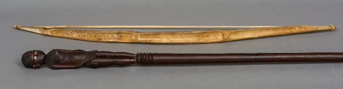 An African carved wood staff Surmounted with a tribes woman; together with a bamboo bow.