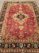 A Tabriz wool carpet The wine red field enclosing a central medallion with stylised pendant