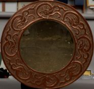An Arts & Crafts copper framed wall glass The bevelled circular plate within a broad frame worked