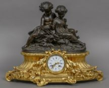A 19th century French patinated and gilt bronze mantel clock Surmounted with two young children,