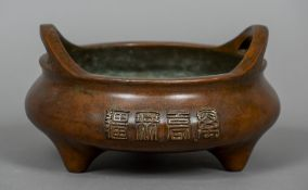 A large Chinese patinated bronze censor Of typical squat form, with calligraphic decorations,