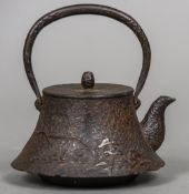 A Japanese cast iron teapot The loop handle above the removable lid and the flared main body