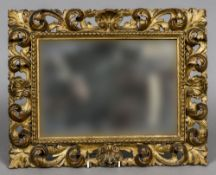 A 19th century Italian carved giltwood framed mirror Of pierced scrolling floral form. 46.