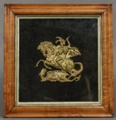 A 19th century gilt metal plaque Worked as St. George slaying the dragon, maple framed and glazed.