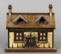 A Victorian painted tea caddy Formed as a cottage. 23 cm wide.