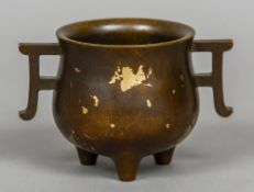 A Chinese bronze twin handled censor With gilt splash decoration, cast mark to base. 8.5 cm high.