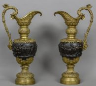 A pair of large patinated and gilt bronze ewers Each decorated in the round with classical