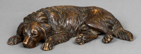 A Blackforest carved dog Modelled in recumbent position, set with glass eyes. 30 cm wide.