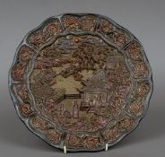 A Chinese lacquered plate Worked with figures and pagodas in a river landscape within floral carved