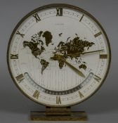 A Kienzle Automatic World Time desk clock Of typical circular form, standing on a plinth base.