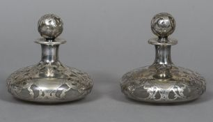 A pair of unmarked silver overlay clear glass scent bottles Each of flattened bun form,