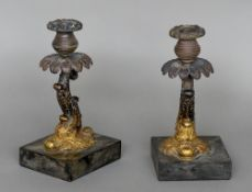 A pair of Regency gilt bronze candlesticks Each formed as scrolling dolphin,